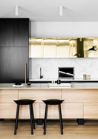 Luxueuse crédence en marbre gris pour cette cuisine design. Assortie au plan de travail, à la façade aspect feuille d'or et aux meubles en bois exotiques