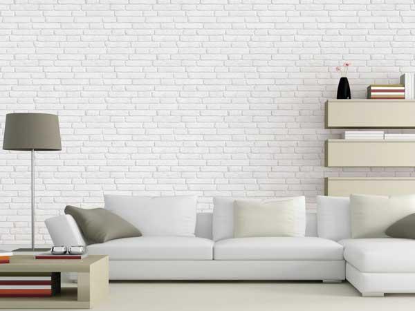 Papier peint intissé impression pierre blanche pour donner une touche indus au canapé d'angle blanc. Lumineux et facile à poser, ce papier peint salon à tout bon