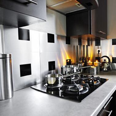 Crédence de cuisine faite avec des carreaux adhésif aluminium finition intox brossé. Ici avec un plan de travail en pierre et des meubles de cuisine design