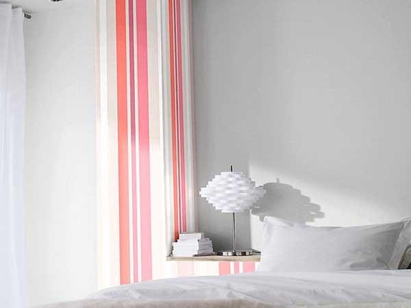 Un lé de papier peint à rayures taupe et rose pour une déco chambre contemporaine. Posé sur un seul pan de mur ce papier peint coloré habille la pièce blanche