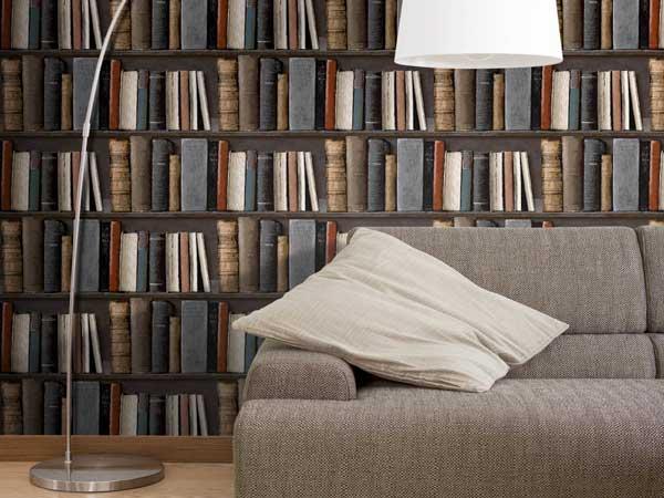 Un papier peint salon vinyle intissé trompe l'oeil bibliothèque décore la pièce. Luminaire design blanc et canapé en tissu taupe complètent cette déco cosy