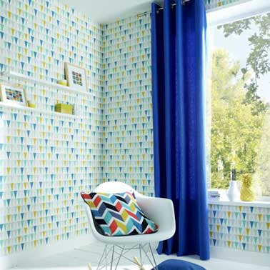 Un papier peint vintage inspiration scandinave à motifs bleu et jaune habille les murs du salon. Marié avec un rideau bleu et un coussin dessin géométrique