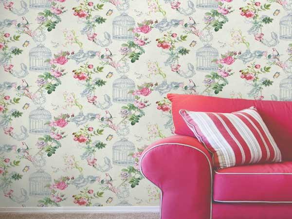 Déco de salon vintage avec un papier peint intissé motifs fleurs roses. Une note rétro et chaleureuse en accord avec le grand canapé en velours framboise