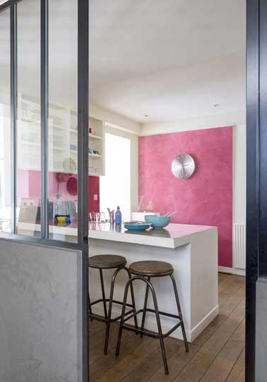 Peinture à effet nacré rouge dans cuisine ouverte mixée avec une couleur ardoise sur le soubassement de la porte verrière. Look industriel avec tabouret de bar en bois et détail inox.