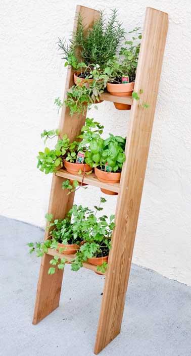 Une échelle en bois relooké pour recevoir des pots de plantes et faire un jardin potager suspendu inattendu. A poser contre le mur d'un balcon ou d'une terrasse.