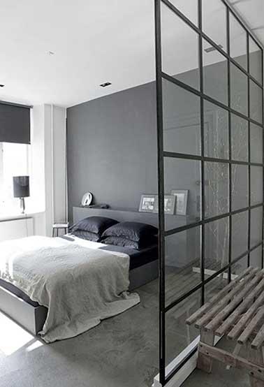 Une verrière intérieure pour créer un coin dressing dans une chambre parentale. Sa structure quadrillée noir se marie avec les oreillers, le rideau et la lampe de chevet design