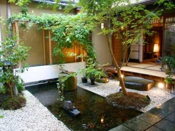 Jardin zen d'inspiration minimaliste composé avec des éclairages d'extérieurs, du gravier blanc et un bassin avec fontaine en bois.