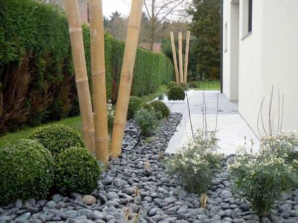 Belle allée de jardin zen faite avec un parterre de galets gris rythmé par des boules de buis des touffes de plantes vivaces et du bambou.