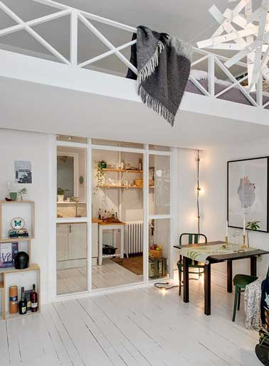 Dans ce petit appartement une verrière intérieur est installée sous la mezzanine pour délimiter ia cuisine du salon. Sa structure peinte en blanc est complètement intégrée à la pièce