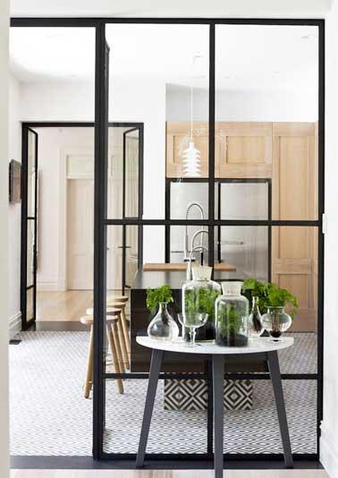 Une cuisine isolée avec deux verrières d'intérieures. Leurs structures métalliques sont coordonnées au carrelage sol et îlot central à motifs géométriques noirs et blancs.
