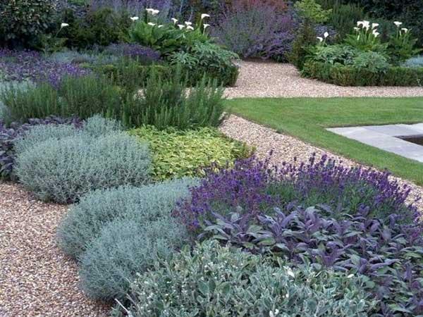 Un jardin zen réalisé avec plusieurs parterre de plantes méditerranéennes entouré de gravillons colorés. Composition symétrique pour entourer un bassin d'extérieur.