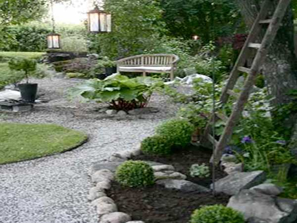 Allée de jardin zen faite avec du graviers blancs et des pierres autour de massif de plantes vertes. Buis, bananier et banc en bois composent ce chemin colorée.