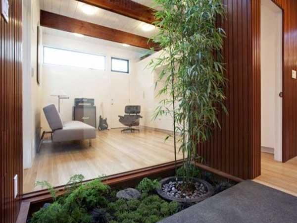 Terrasse en bois pour le jardin zen avec ce petit coin de verdure bordé de palissades en bois. Bambou en pot et tapis de mousses apaisent la composition.