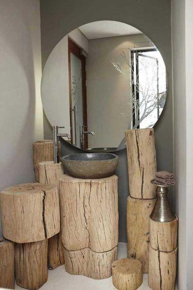 Des robinets chromés design et une vasque en pierre s'offrent une seconde vie sur ces meubles de salle de bain fabriqués avec des rondins de bois. Super original !