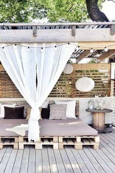 Ambiance cocooning et déco extérieur nature, avec ce salon de jardin en palette installé sous le patio d'une terrasse en bois
