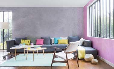 Deux couleurs de peinture nacrée rose et grise s'accordent à l'ambiance douce du séjour créée avec deux tables cigognes en bois clair, une chaise scandinave et des coussins colorés