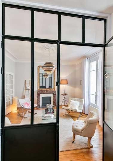 Un salon séparé d'une entrée grâce à une verrière d'intérieure. Sa structure métallique est valorisée par parquet et murs blancs et modernise la déco de la pièce