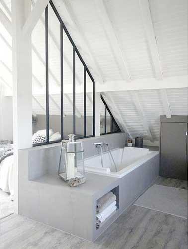 Une verrière intérieure est posée sur une cloison tête de lit de la suite parentale. Aménagée sous pente, elle permet de séparer la salle de bain de la chambre.