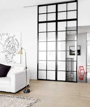 Le salon gagne en intimité avec sa verrière intérieure quadrillée montée sur porte coulissante. En contraste sur les murs blancs, elle impose son style industriel dans le salon
