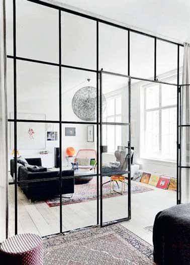 Coin cosy et grand salon cohabitent ensemble grâce à une verrière intérieure posée dans la pièce. Sa structure métallique quadrillée rythme la pièce et amène des couleurs à la pièce