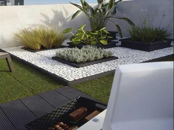 Un coin zen sur la terrasse délimitée avec des galets blancs et plusieurs carrés de plantes vivaces et de plantes grasses
