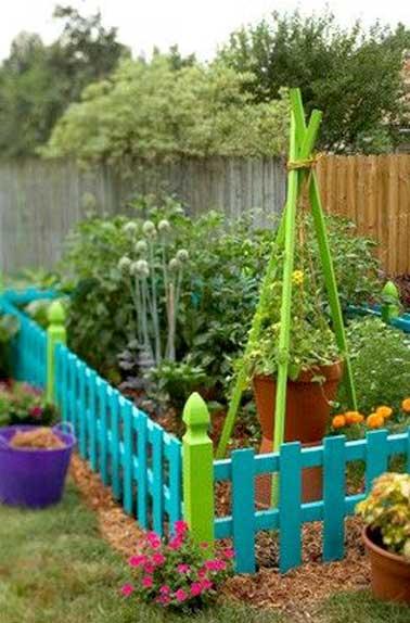 Petit jardin potager délimité par clôture en bois colorée agrémentée de pieds décoratifs. A l'intérieur des trépieds bois reçoivent une suspension pour plante grimpante.