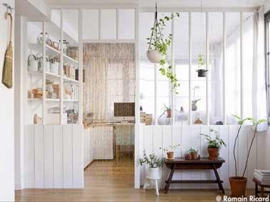 La verrière d'intérieur en bois blanc donne un look scandinave à la déco. Installée pour délimiter l'espace bureau du reste de la pièce elle se ferme avec un rideau de perle en bois