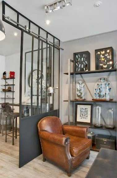 Complètement dans le ton industriel de la pièce, cette verrière d'intérieure divise le salon. Sa structure métallique se marie aux étagères en métal et au parquet blanchi