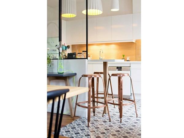 Cette verrière d'intérieur ainsi que le carrelage géométrique viennent séparer avec délicatesse une cuisine moderne et le salon. Une tableau haute le long des vitres est réservée aux petits déjeuners.