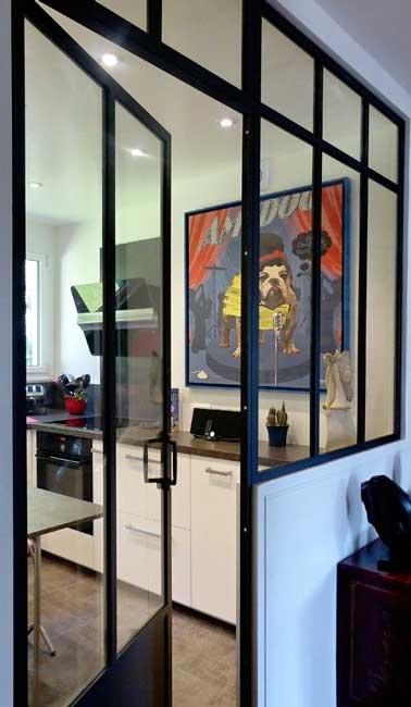 une verrière intérieure avec porte battante sépare l'espace cuisine de l'entrée. En verre et en acier noir, elle ajoute une note industrielle à la déco.