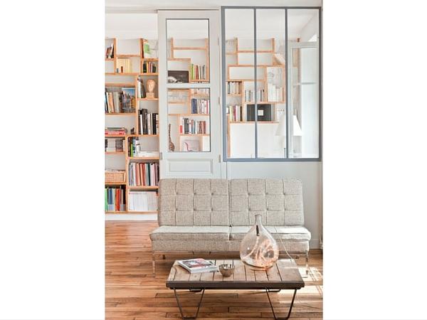 La verrière a été montée sur un mur portant une porte vitrée et joue sur la transparence avec une pointe d'humour dans ce bel intérieur contemporain.
