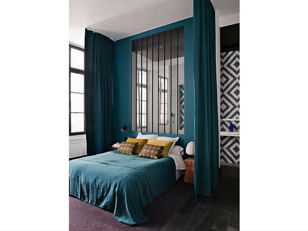 La verrière contribue à mieux définir l'espace à l'intérieur de cette chambre. Les rideaux et le papier peint que l'on peut observer par transparence jouent sur les effets d'optique.