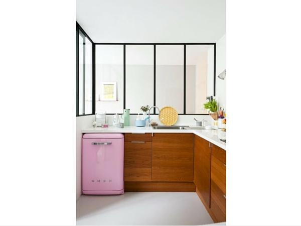 Une cuisine borgne gagne en lumière grâce à l'installation d'une verrière intérieure au style industriel. Elle vient casser le côté très féminin apporté par le réfrigérateur rose vintage en apportant du rythme.