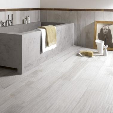 La déco de cette petite salle de bain est assurée par une baignoire en béton grise et un carrelage imitation bois, moins cher que le parquet, mais tout aussi esthétique.