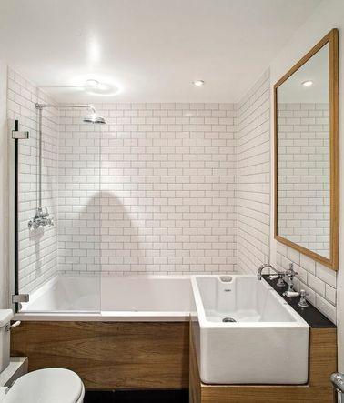 Dans une salle de bain rétro rencontre élégante de carrelage métro sur tous les murs et du bois en habillage de baignoire et de plan vasque.