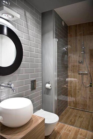 Dans cette salle de bain grise, on a appliqué un joint blanc sur le carrelage métro gris des murs qui répond à celui du carrelage imitation bois de la douche et du sol