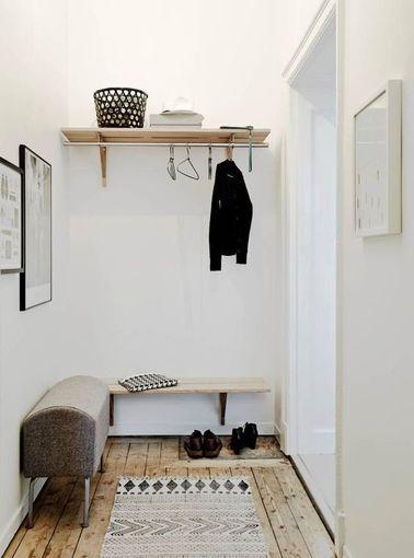 Déco épurée dans le hall entrée d'un appartement suédois. Un banc vintage, une étagère basse pour poser ses clés et rangement sur étagère haute avec penderie.