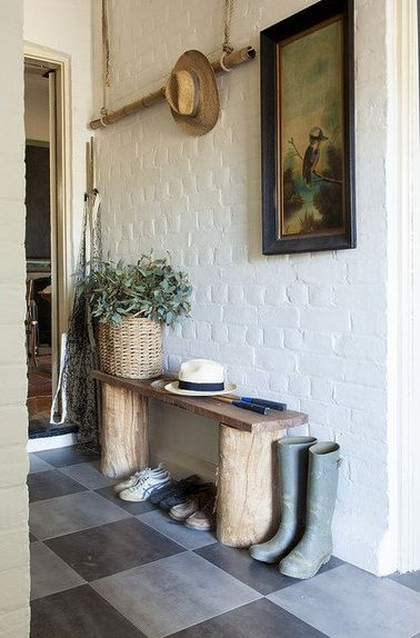 Ambiance déco rustique dans un hall d'entrée en briques blanches avec un banc rangement chaussures fait de 2 rondins et une planche