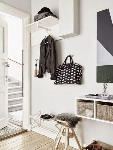 Un hall d'entrée qui donne sur le salon en s'harmonisant à son ambiance déco. Idée gain de place : la tringle sous l'étagère utilisée en profondeur pour pendre sa veste.