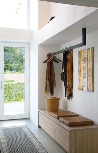 Un hall d'entrée lumineux grâce à la porte d'entrée en verre et rangement optimisé avec un meuble bas placé dans une alcôve et une barre en fer pour suspendre les vêtements.