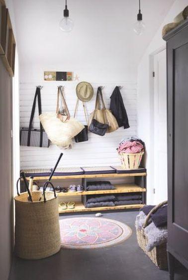 Ce hall d'entrée campagne chic évoque les vacances. Patères fixées sur lambris bois, coussins sur le meuble à chaussures et tapis rond style mandala