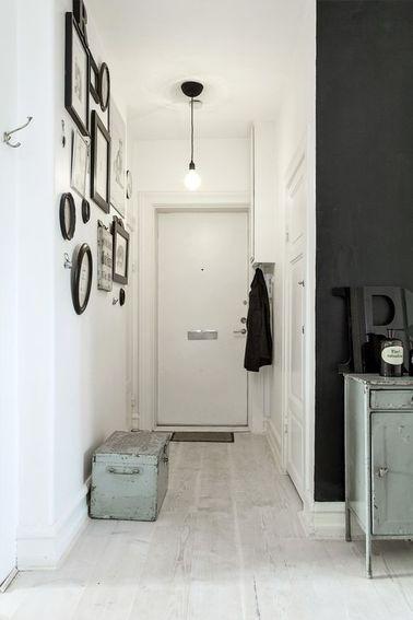 Un hall d'entrée ouvert sur le couloir décoré en noir et blanc. ! Placard et murs peints en blanc, malle de récup en range chaussures et cadres photo noir regroupés en composition déco