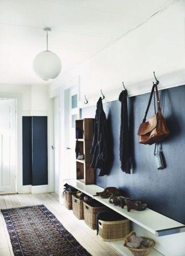 Une déco de hall d'entrée hyper bien aménagée avec des rangements pour les chaussures et manteaux tous simples fait de patères, paniers et plateau stratifié.
