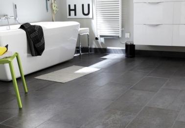 La déco de cette salle de bain grise et blanche est facile à refaire chez vous avec un sol en carrelage effet béton facile à vivre et une baignoire îlot aux lignes design