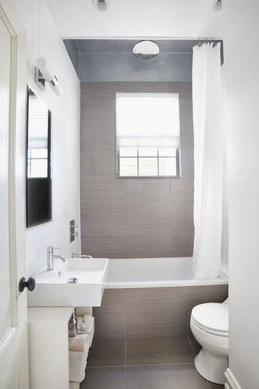 Apaisante et ultra lumineuse, cette petite salle de bain grise est 100% optimisée avec sa petite baignoire aménagée au fond de la pièce et un meuble de rangement pratique