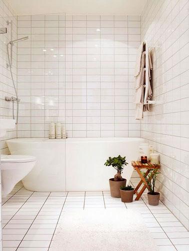 Total look blanc dans cette salle de bain recouverte de carrelage du sol au plafond ! On craque pour la baignoire îlot et les toilettes surélevés pour une ambiance épurée
