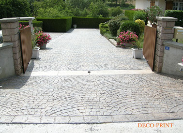 Disposés en courbes, les motifs du béton imprimé devant la maison donnent du cachet à l'entrée ! Une déco extérieure originale avec un sol hyper esthétique !