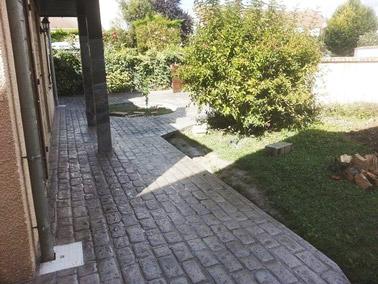 Verdure et béton imprimé à motif en briques s'accordent parfaitement dans la déco extérieure derrière la maison ! Un sol qui apporte de la valeur ajoutée au jardin !