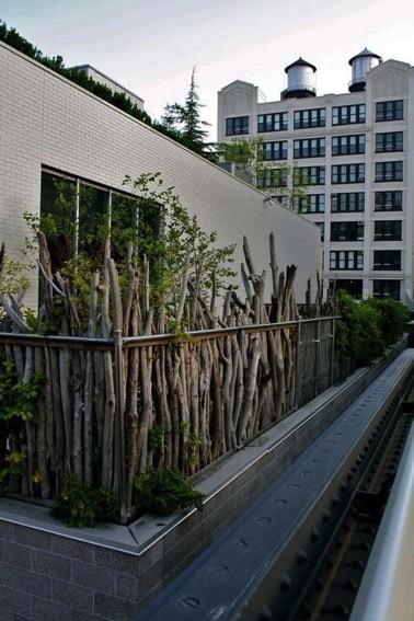 Voilà un brise vue qui donne un style original à la déco du balcon ! Réalisé avec des branches de bois, le brise vue offre de l'intimité à ce petit espace extérieur