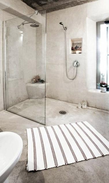 Relaxation assurée dans cette salle de bain lumineuse en béton ciré beige ultra chic ! Une salle de bain déco accueillant une douche italienne pleine d'élégance